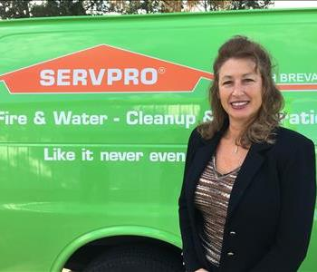 Marketing Manager Andrea in front of green SERVPRO truck