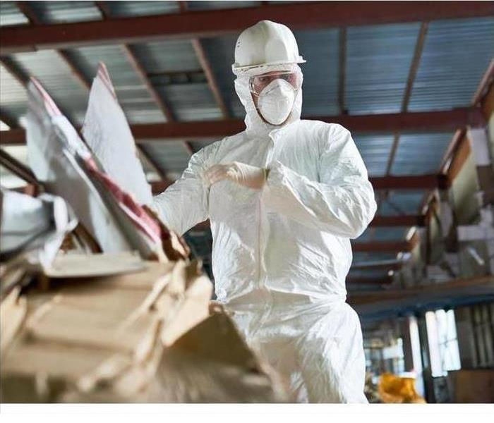 Worker in a biohazard suit cleaning up